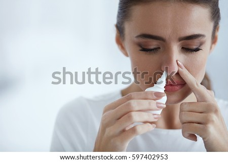 Cold. Portrait Of Beautiful Young Woman Sniffing Nasal Spray Closing One Nostril. Closeup Of Female Feeling Sick With Running Nose Using Sinus Medication For Blocked Nose. Healthcare. High Resolution
