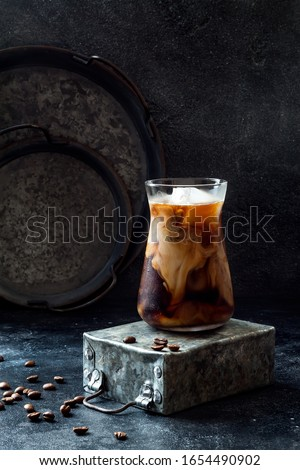 Cold refreshing iced coffee with cream in a tall glass and coffee beans on dark background.