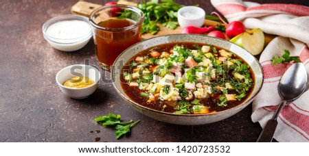Cold Russian Soup Okroshka with sausage, vegetables and kvass in bowl and raw ingredients on dark table. Long wide banner. Space for text. Long wide banner #1420723532