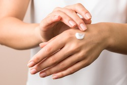 cold season hands skin protection. closeup woman applying protective cream on hands.