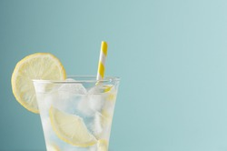 Cold shine sparkling refreshing drink for party with lemon slices, ice cubes, tonic, yellow straw in elegant glass on mint color wall, closeup, edge, half.