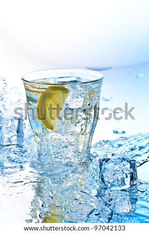 cold soda drink with ice and lemon slashed by water