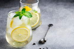 cold sparkling green tea with lemon, mint and ice, glasses on a grey background, summer drinks, lemonade