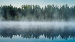 Cold summer morning in the forest with lake, forest reflection and mist on the water surface.