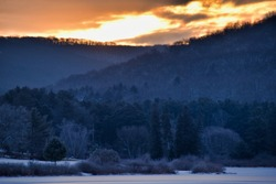 Cold Sunrise Over Tree Covered Hills And Frozen Water With Snow At Red House Lake, Allegany State Park, New York