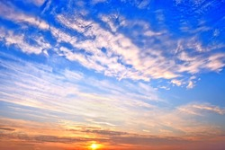 cold sunset sky on winter evening landscape background. Wide panorama cloudscape. Scenic sky with setting sun behind clouds. Nature abstract wallpaper