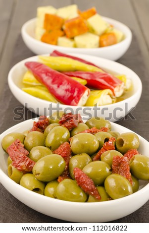 Cold Tapas - Spanish style antipasti with green olives and sun-dried tomatoes, soft cheese stuffed chilies, and cheese cubes with herbs.
