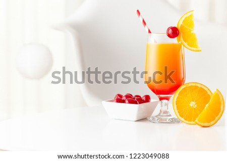 Cold tequila sunrise cocktail with tequila, pomegranate juice and orange juice decorated with slices of orange and maraschino cherries