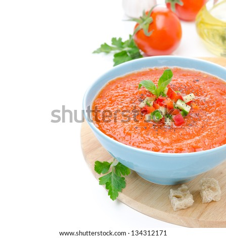 cold tomato soup gazpacho with basil and croutons in a bowl, isolated on a white background close-up