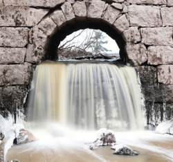 Cold water flowing under stone bridge in winter forming ice and showing sky branches and tree in the background