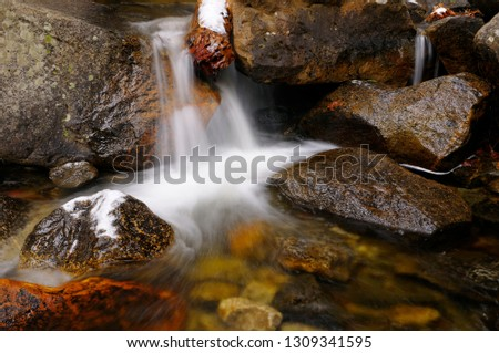 Cold waterfall and whirlpool with snow on rocks on Bridalveil Creek below the Fall in Yosemite Valley