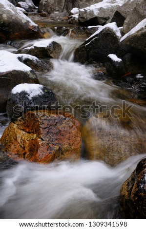 Cold waterfall with snow on rocks on Bridalveil Creek below the Fall in Yosemite Valley