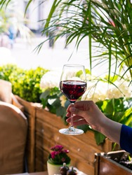 Cold wine in a glass. The girl holds a glass in her hand. Green background. Summer terrace. The sun is shining and it is very hot. Alcoholic beverage. Red wine.