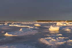 Cold winter evening at the beach. Frozen Baltic Sea, granite rocks covered with ice, tiny icebergs. Sunset skies during golden hour.