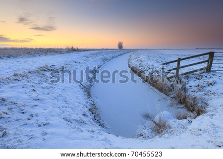 Cold winter landscape with snow at sunset
