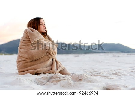 cold woman wraps blanket over herself while sitting on the beach after sunset.