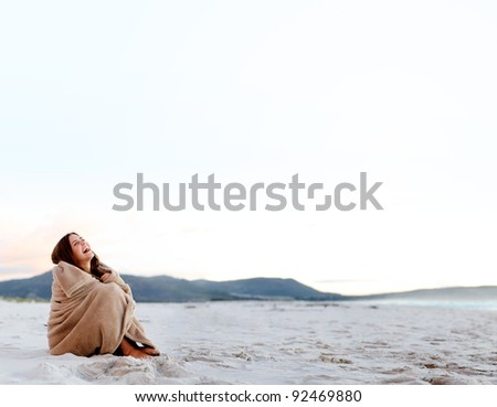 cold woman wraps blanket over herself while sitting on the beach after sunset. copyspace provided by panoramic image
