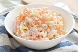 Coleslaw salad with carrot and cabbage on a white bowl.