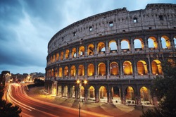 Coliseum at night with colorful blurred traffic lights. Rome - Italy.