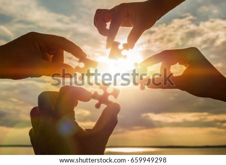 Collaborate four hands trying to connect a puzzle piece with a sunset background. A puzzle in hand against sunlight. One part of the whole. Symbol of association and communication. Business strategy.