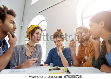 Collaboration and brainstroming concept. Portrait of interracial friends gathering together sitting at table in classroom surrounded with books having debates expressing their opinions and views. Photo stock ©