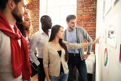 Collaboration is a key to best results. Group of young modern people in smart casual wear planning business strategy while young woman pointing at infographic displayed on the white wall in the office