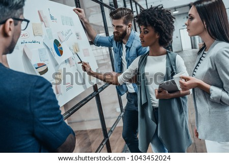 Collaboration is a key to best results. Group of young modern people in smart casual wear planning business strategy while young woman pointing at infographic displayed on the glass wall in the office - Shutterstock ID 1043452024