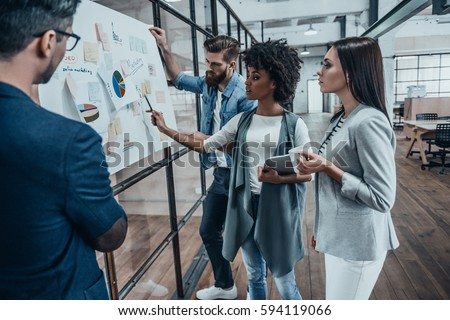 Collaboration is a key to best results. Group of young modern people in smart casual wear planning business strategy while young woman pointing at infographic displayed on the glass wall in the office