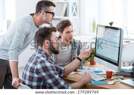 Collaboration is a key to success. Three young business people discussing something while looking at the computer monitor together