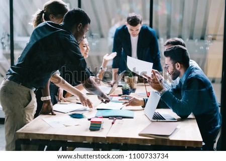 Collaborative process of multicultural skilled students during brainstorming meeting in office.Diverse team of young people dressed in formal wear cooperating on developing common design project - Shutterstock ID 1100733734