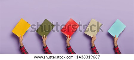 Collage image of various colorful textbooks in male hands isolated over purple background. Books for studying. Education concept. Notepads for writing notes with colored bookmarks. Horizontal shot