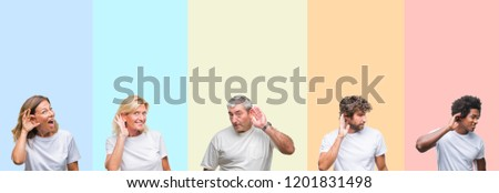Collage of group of young and middle age people wearing white t-shirt over color isolated background smiling with hand over ear listening an hearing to rumor or gossip. Deafness concept. ストックフォト ©