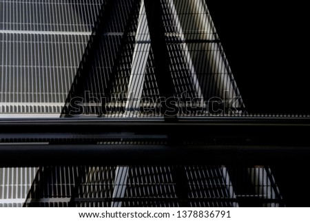 Collage photo of metal walls, girders and grid structures resembling bridge or industrial building exterior. Abstract modern architecture background in darkness with geometric structure of triangles. #1378836791