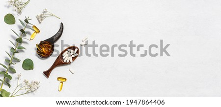 Collagen capsules and omega 3 capsules for skin care and beauty in the wooden spoon on white background with herbs and flowers. Health care concept. Long banner format. Foto stock ©