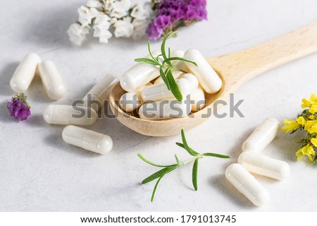 Collagen capsules for skin and beauty in the wooden spoon with herbs and flowers on white marble table close up. Health care concept. Foto stock ©