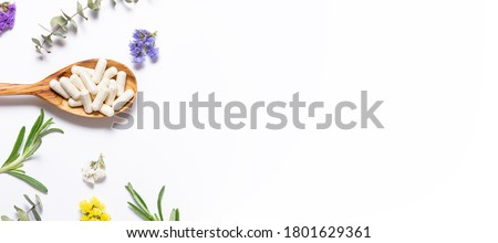 Collagen capsules for skin care and beauty in the wooden spoon on white background with herbs and flowers. Health care concept. Long banner format. Foto stock ©