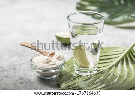 Collagen Powder and glass of water with  slice of Lime; Vitamin C . Collagen supplements may improve skin health by reducing wrinkles and dryness.