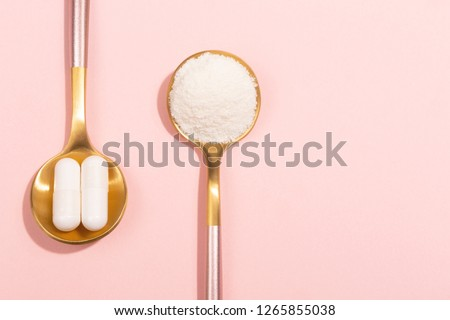 Collagen powder and pills on pink background. Extra protein intake. Natural beauty and health supplement for skin, bones, joints and gut. Plant or fish based. Flatlay, top view. Copy space text.