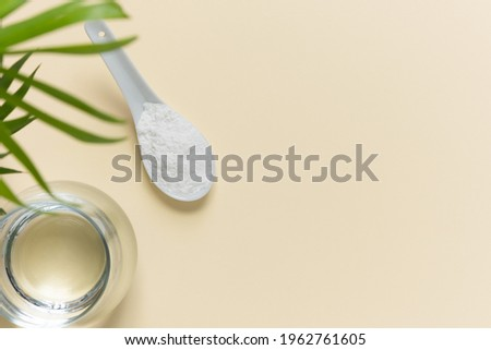 Collagen powder in a spoon and a glass of water on a beige background with a copy space. Extra protein intake. Photo stock ©