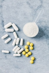 Collagen powder, Proline and MSM (Sulfur) capsules and Vitamin C tablets. Supplements to support collagen production. Bright stone background. Top view.