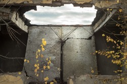 Collapsed roof concrete floor of abandoned building. Through hole in the ceiling overlooking the cloudy sky