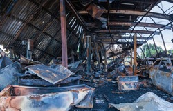 Collapsed roof, mangled scrap and exposed steel in burned out auto garage