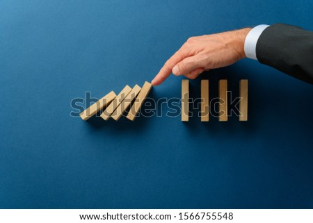 Collapsing dominos being stopped my a crisis business manager in a conceptual image. Over navy blue background with copy space. Stock photo ©