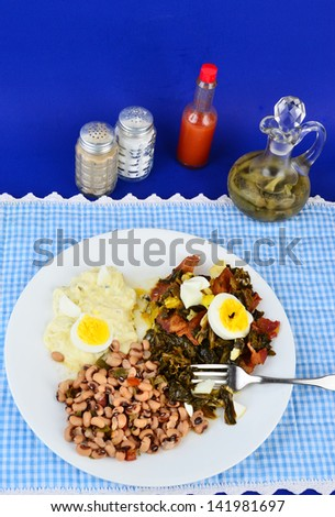Collard greens seasoned with bacon drippings and salt pork and garnished with boiled egg on white plate with potato salad and black eyed peas.  Blue gingham setting adds to Southern or Country Feel.