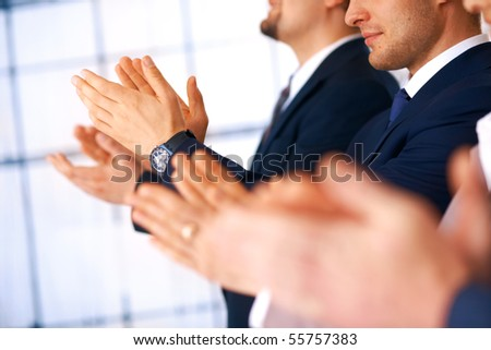 Colleagues applauding during a business meeting, focus on the hands. - stock photo