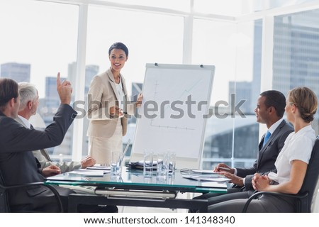 Colleagues Asking A Question To A Businesswoman During A Presentation