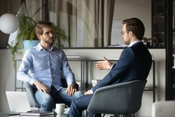 Colleagues businessmen discussing project strategy, sharing ideas, sitting in armchairs in modern office, business partners negotiating startup, hr manager holding interview with candidate
