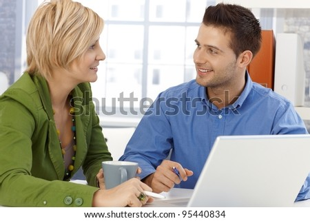 Colleagues chatting, sitting together at office table, smiling.?