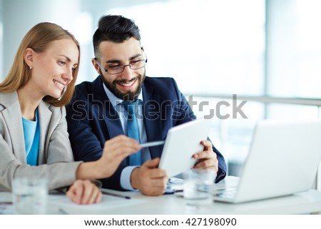 Colleagues discussing data on touchpad - Shutterstock ID 427198090