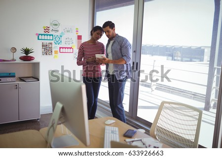 Colleagues discussing over digital tablet while standing in office #633926663